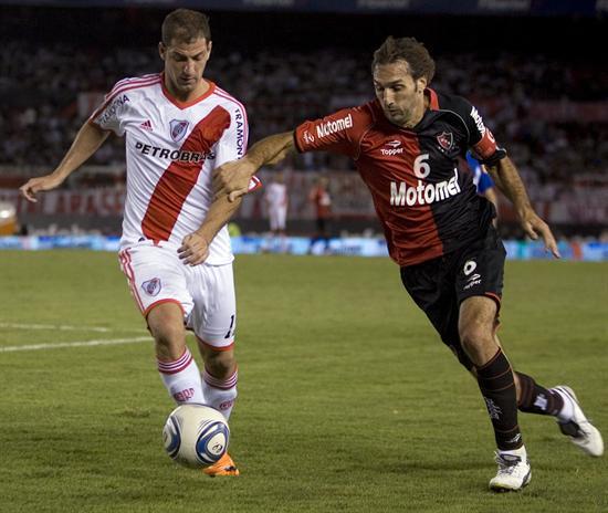 El jugador de River Plate Leandro Caruso (i) disputa el balón con Rolando Schiavi (d) de Newell´s Old Boys. Foto: EFE