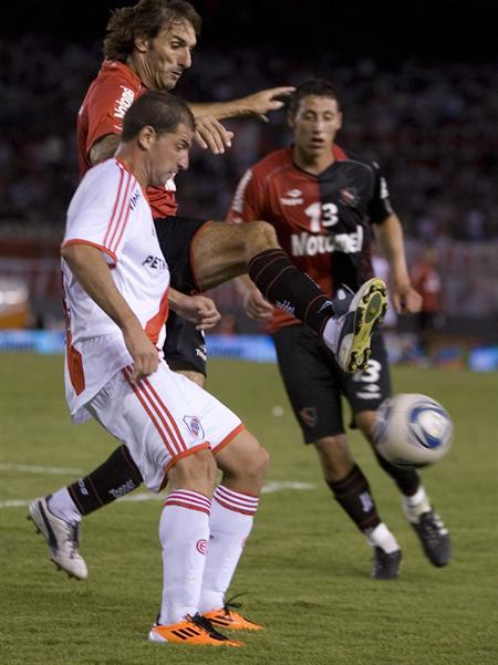 El jugador de River Plate Leandro Caruso (i) disputa el balón con Rolando Schiavi (d) de Newell´s. Foto: EFE