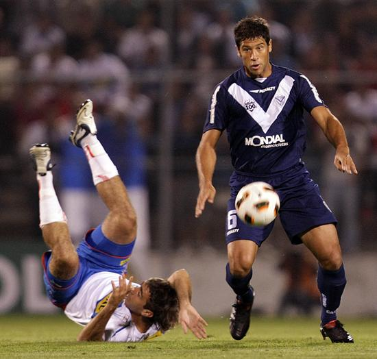 El jugador de Universidad Católica Lucas Pratto (i) cae ante la marca de Sebastián Domínguez (d) de Vélez Sarsfield/EFE