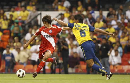 El defensa de América Juan Carlos Valenzuela (i) disputa el balón con el jugador Ciro Rius, de Argentinos/EFE