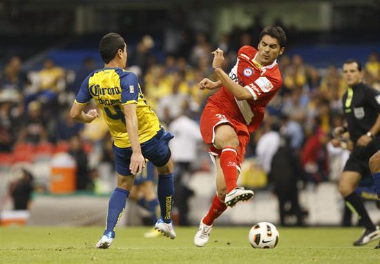 El defensa de América Oscar Rojas (i) disputa el balón con el delantero Santiago Salcedo (d), de Argentinos Jrs/EFE