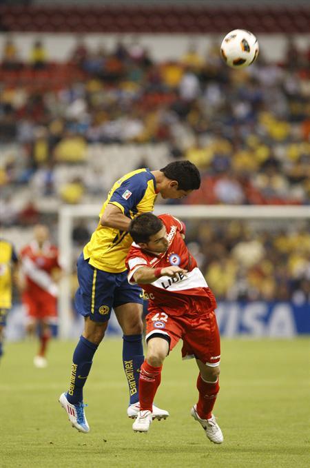 El defensa de América Oscar Rojas (i) disputa el balón con el delantero Franco Niell (d), de Argentinos Jrs/EFE
