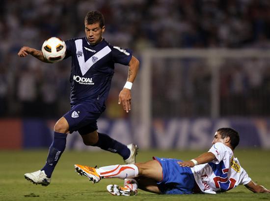 El jugador de Universidad Católica Felipe Gutiérrez (d) hace la marca a Héctor Canteros (i) de Vélez Sarsfield/EFE