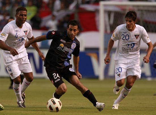 El jugador Carlos Falcón (c) de Godoy Cruz domina el balón con la marca de Enrique Vera (d) y Ulises de la Cruz/EFE