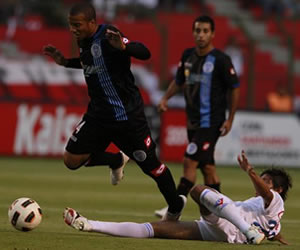 El jugador de Liga de Quito Enrique Vera (d) marca a Juan Carlos Falcón (i), de Godoy Cruz/EFE