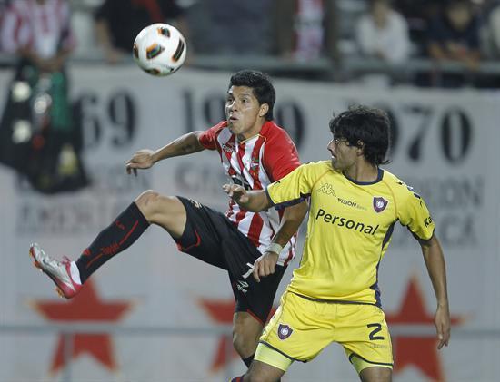El jugador de Estudiantes de La Plata de Argentina Enzo Pérez (i) recibe la marca de César Benítez de Cerro Porteño/EFE