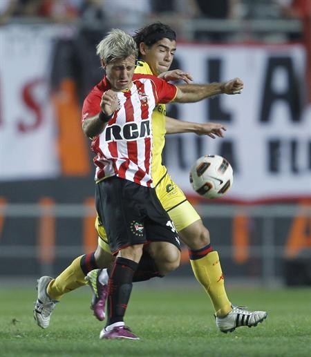 El jugador de Estudiantes de La Plata de Argentina Gastón Fernández (i) lucha por el balón con Rodrigo Burgos de Cerro/EFE