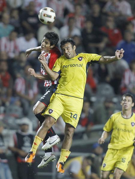 El jugador de Estudiantes de La Plata de Argentina Pablo Barrientos (i) lucha por el balón con Javier Villarreal (c) de Cerro Porteño/EFE
