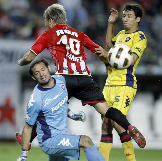 El jugador de Estudiantes de La Plata Gastón Fernández (c) lucha por el balón/EFE