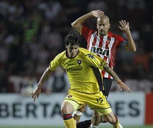 El jugador de Cerro Porteño Jonathan Fabbro (c) se lleva el balón ante la marca de Enzo Pérez (i) y Juan Sebastián Verón (d) de Estudiantes/EFE