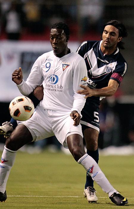 El jugador de Liga de Quito Wálter Calderón (i) dispusta el balón con Fabián Cubero (d) de Vélez Sarsfield/EFE