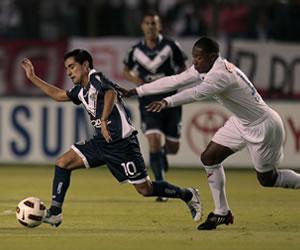 El jugador de Liga de Quito Diego Calderón (d) dispusta el balón con Maximiliano Moralez (i) de Vélez Sarsfield/EFE