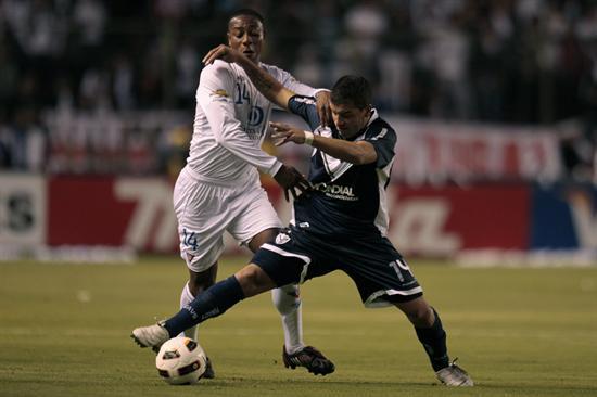 El jugador de Liga de Quito Diego Calderón (i) dispusta el balón con Héctor Canteros (d) de Vélez/EFE