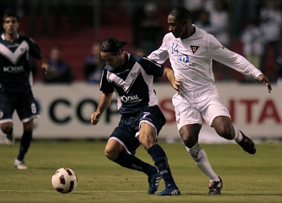 El jugador de Liga de Quito Diego Calderón (d) dispusta el balón con Juan Martínez (i) de Vélez/EFE