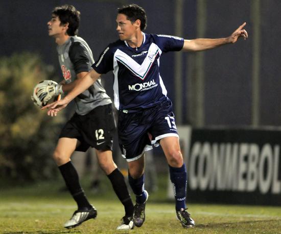 Guillermo Franco (d) celebra después de anotar un gol ante el portero de Libertad, Tobias Vargas/EFE