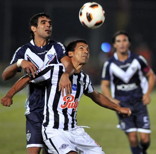 El jugador de Vélez Sarsfield Augusto Fernández (i) marca a Sergio Aquino (c), de Libertad/EFE