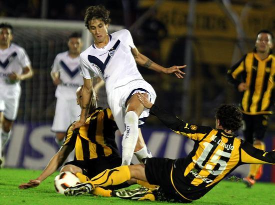 El jugador de Vélez Sarsfield Ricardo Álvarez (c) disputa el balón con Guillermo Rodríguez (i) y Matías Corujo/EFE