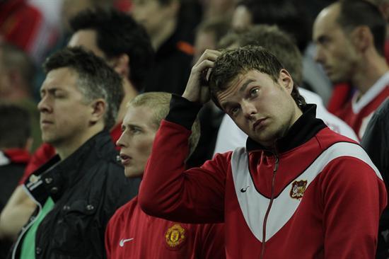 Aficionados del Manchester United reaccionan tras la derrota del equipo en la Liga de Campeones/EFE