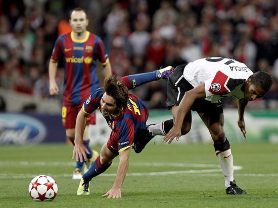 El delantero argentino del FC Barcelona Lionel Messi (i) conduce el balón presionado por el centrocampista ecuatoriano del Manchester United Antonio Valencia/EFE