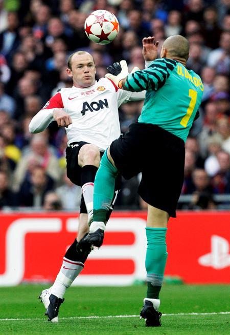 Wayne Rooney (i) del Manchester United lucha por el balón con el portero del FC Barcelona Victor Valdés/EFE
