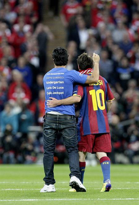 Un aficionado invade el campo de juego y saluda a Lionel Messi (d)/EFE