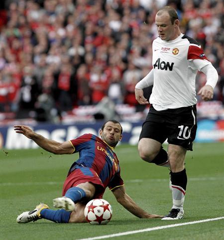 El defensa argentino del FC Barcelona Javier Mascherano (i) pugna por el balón con el delantero inglés del Manchester United Wayne Rooney/EFE