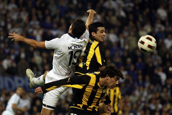 El jugador de Velez Sarsfield Fernando Ortiz (i) disputa el balón ante Alejandro González (arriba, d) y Matías Corujo (abajo, d) de Peñarol. Foto: EFE