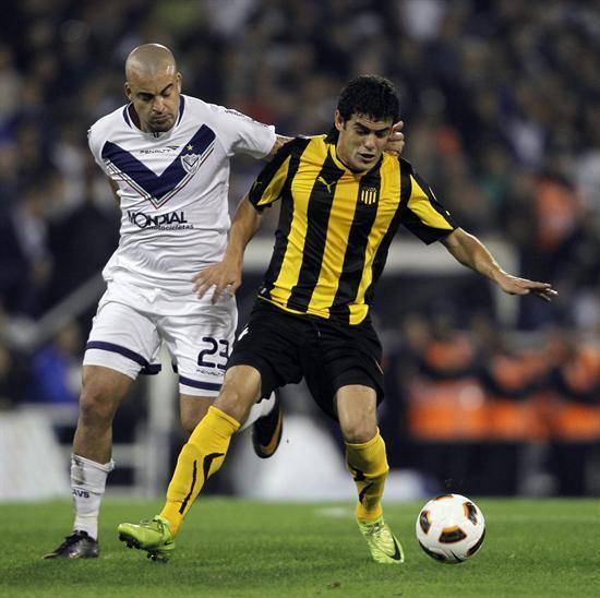 El jugador Santiago Silva (d) de Vélez Sarsfield disputa un balón con Luis Aguiar (i) de Peñarol. Foto: EFE