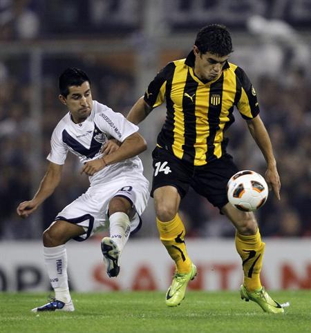 El jugador Maximiliano Moralez (i) de Vélez Sarsfield disputa un balón con Luis Aguiar (d) de Peñarol. Foto: EFE