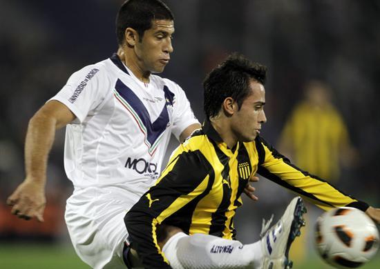 El jugador Sebastián Domínguez (i) de Vélez Sarsfield disputa un balón con Alejandro Martinuccio (d) de Peñarol. Foto: EFE