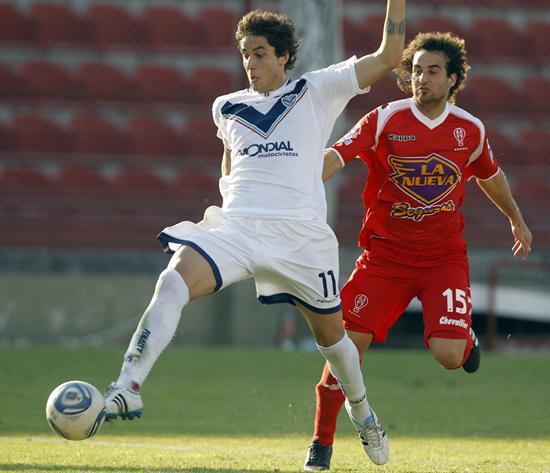 El jugador del Huracán Kevin Cura (d) disputa el balón con Ricardo Álvarez (i), del Vélez Sarsfield. Foto: EFE