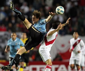 El jugador de fútbol de la selección de Uruguay Sebastián Coates (izq) disputa el balón ante su rival de Perú/EFE