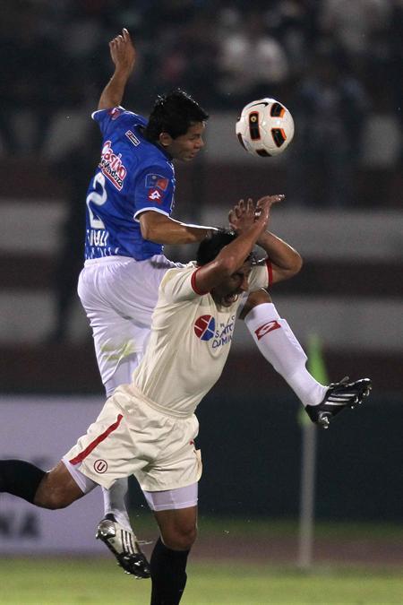 Johan Fano (d) de Universitario de Deportes de Perú, disputa la pelota con Leonardo Sigali (i) de Godoy Cruz. Foto: EFE