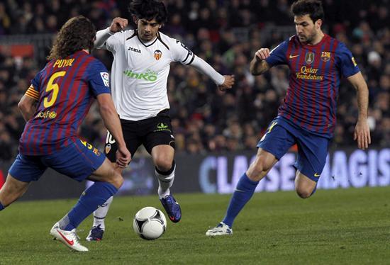 Los jugadores del Barcelona Cesc Fabregas (d) y Carles Puyol (i), intentan robar el balón a Banega. EFE