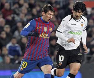 El delantero argentino del Barcelona Lionel Messi (i) conduce el balón ante la presencia del centrocampista del Valencia Éver Banega. EFE