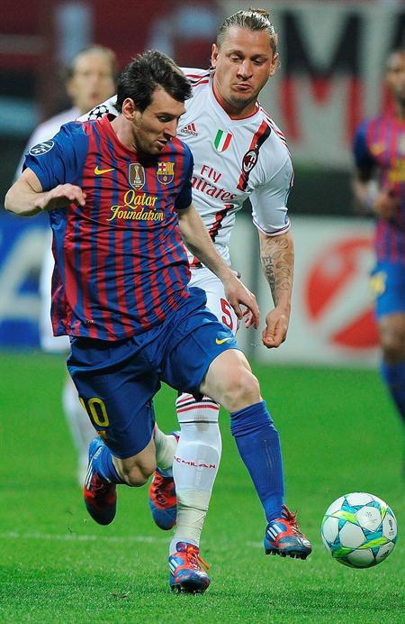 El jugador del AC Milán, Philippe Mexes (dcha), pelea por el control del balón con el delantero argentino del FC Barcelona, Leo Messi. Foto: EFE