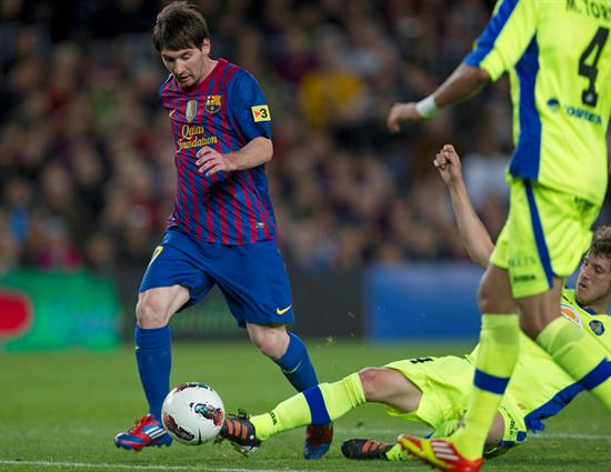 El delantero argentino del F. C. Barcelona, Leo Messi, se lleva el balón ante un defensor del Getafe. EFE
