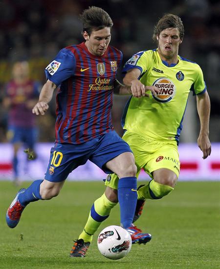 El delantero argentino del F. C. Barcelona, Leo Messi (i), se lleva el balón ante el jugador del Getafe, Rubén Pérez. EFE