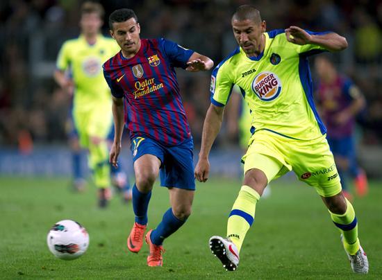 """El delantero del F. C. Barcelona, Pedro (i), pelea un balón con el defensor argentino del Getafe, el """"Cata"""" Díaz. EFE"""