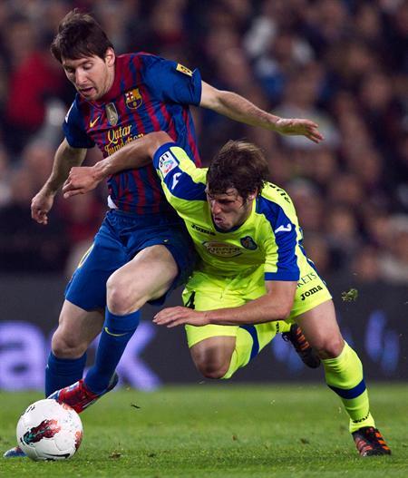 El delantero argentino del F. C. Barcelona, Leo Messi (i), disputa el balón ante el jugador del Getafe, Rubén Pérez. EFE