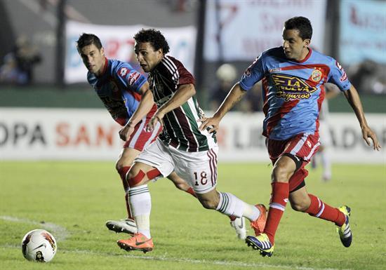 El jugador de Fluminense, Wellington Nem (i), disputa el balón con Jorge Ortiz (c) de Arsenal. Foto: EFE