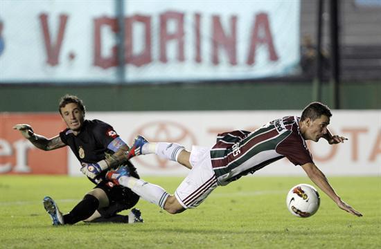 El arquero de Arsenal, Cristian Campestrini (i), le comete una falta a Thiago Neves (d) de Fluminense. Foto: EFE