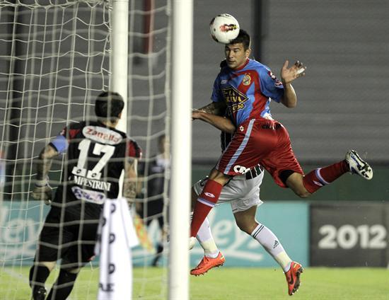 El jugador de Fluminense, Rafael Moura (d), cabecea el balón frente al arco de Arsenal. Foto: EFE