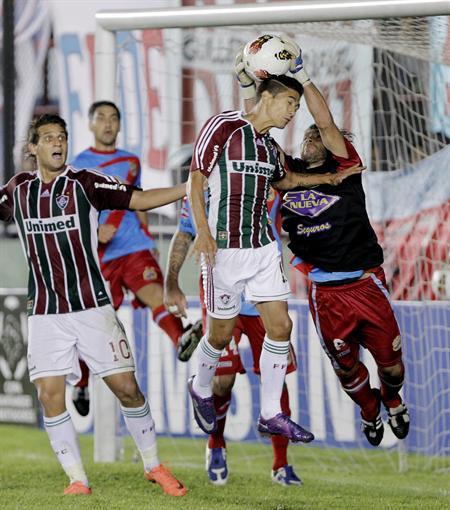 El jugador de Fluminense, Digao (c), cabecea el balón ante la marca de Diego Torres (d) de Arsenal. Foto: EFE