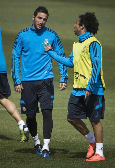 El delantero argentino del Real Madrid, Gonzalo Higuaín (i), conversa con el defensa brasileño Marcelo Vieira, durante el entrenamiento previo a la Champions. Foto: EFE
