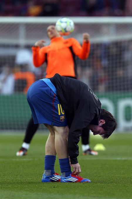 El delantero argentino del Barcelona Lionel Messi se ata las botas, previo la juego con el Chelsea. Foto: EFE