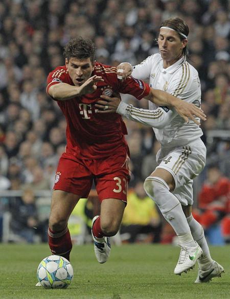 . MADRID, 25/04/2012.- El delantero del Bayern de Munich, Mario Gómez (i), intenta controlar el balón ante la oposición del defensa del Madrid, Sergio Ramos. Foto: EFE