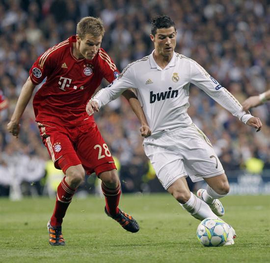 El delantero portugués del Real Madrid, Cristiano Ronaldo (d), controla el balón junto a Holder Badstuber, del Bayern de Munich. Foto: EFE