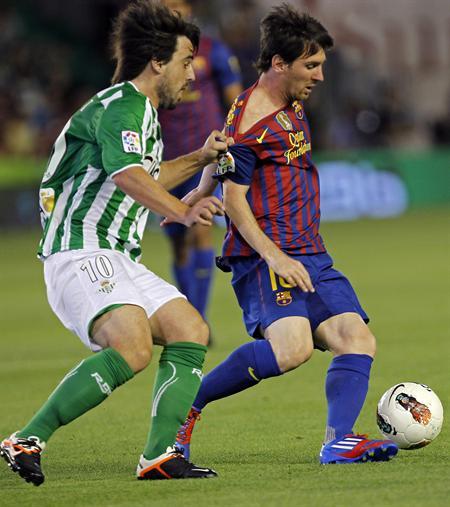 El delantero argentino del FC Barcelona Lionel Messi (d) protege el balón ante el centrocampista del Real Betis Beñat Etxebarria. Foto: EFE