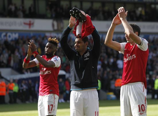 Los jugadores del Arsenal, Alexandre Song (izq), André Santos (c) y Robin van Persie (dcha) celebran con su afición la victoria frente al West Bromwich. Foto: EFE